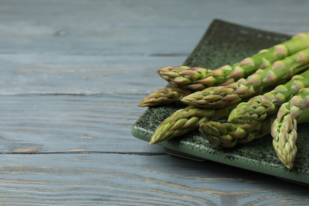Plate with green asparagus on wooden
