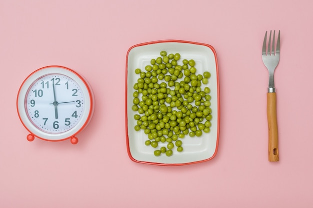 A plate with green peas, a fork and an alarm clock on a pink background. the concept of a healthy diet for weight loss.