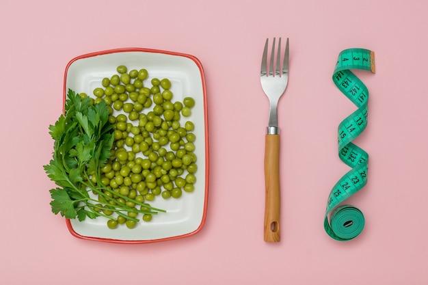 Тарелка с зеленым горошком, вилкой и измерительной лентой на розовом фоне. концепция здорового питания для похудения.