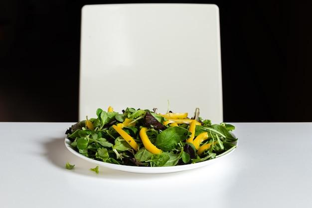 Тарелка с зеленым салатом и желтым перцем на белом кухонном столе, крупный план, концепция здорового питания и диеты
