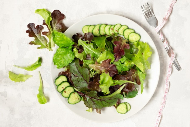 A plate with green salad leaves, sesame seeds and cucumber slices, a tape-measure wrapped around a fork on the right