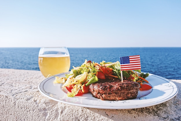 Plate with grilled juiciest burger meat and vegetables decorated with usa flag