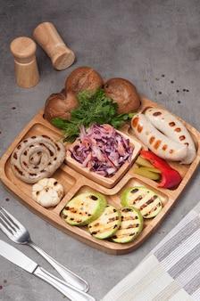 구운 소시지, 호박, 붉은 양배추, 빵이 있는 접시
