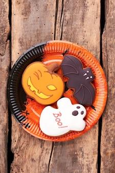 木製の背景にハロウィーンのクッキーでプレート。