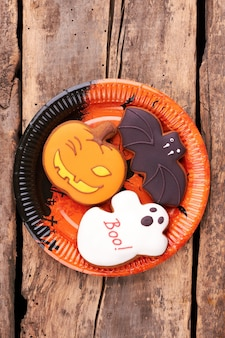 Plate with halloween cookies on wooden background.