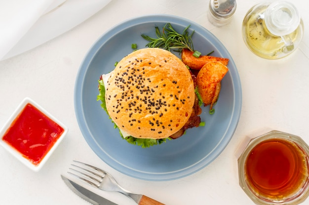 Тарелка с гамбургером и соусом рядом