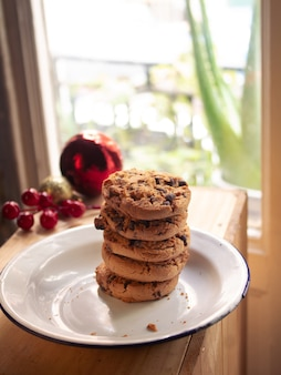 Plate with handmade chocolate chip cookies inside the house with christmas decorations nearby