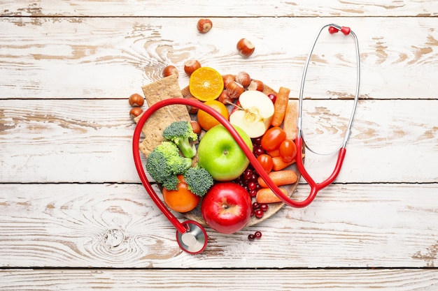 Plate with healthy products and stethoscope on white surface wooden surface