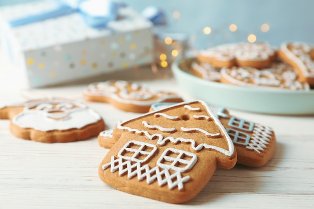 Plate with homemade christmas cookies, gift boxes on white wooden table, on blue. closeup