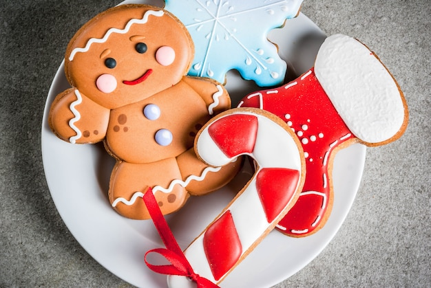 Plate with homemade colorful glazed christmas cookies on stone gray table, top close view
