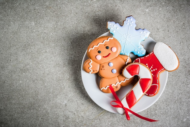 Plate with homemade colorful glazed christmas cookies on stone gray table, top view  copyspace