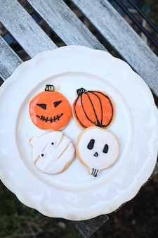 Plate with homemade cookies decorated for halloween on a wooden table on a background of natural fallen autumn leaves plate with homemade cookies decorated for halloween on a wooden table on a backgro