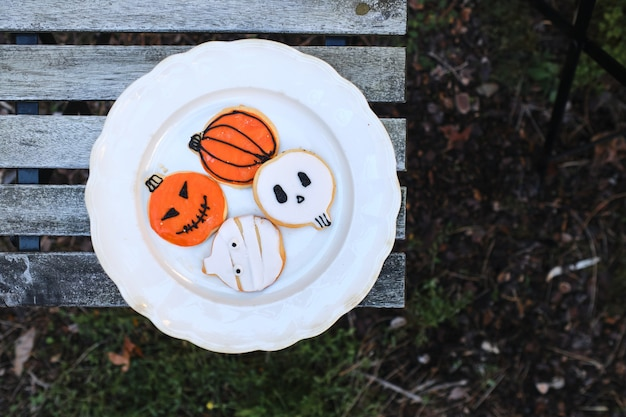 Plate with homemade cookies decorated for halloween on a wooden table on a background of natural fallen autumn leaves