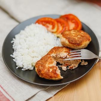 木製のテーブルにご飯と自家製サーモンフィッシュカツレツのプレート。