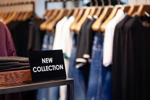銘板付きプレートブティックの棚の新しいコレクション、ハンガーにカラフルな男性用、女性用の服を備えた衣類ラック。コンセプトの高級店、ショッピングモール、店舗販売、小売店、アウトレット。