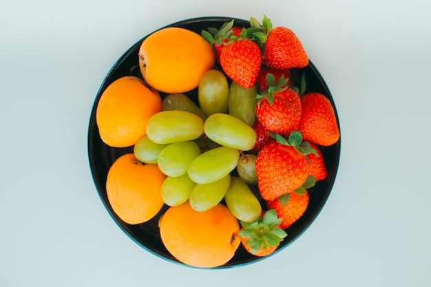 The plate with juicy strawberries, ripe grapes and sweet medlar