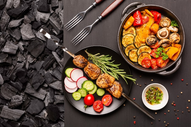 Plate with kebab and fresh vegetables, frying pan with grilled vegetables on a black wooden table top with a background of charcoal. top view.