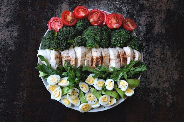 Plate with a keto diet food. a set of products for the ketogenic diet on a plate. cherry tomatoes, boiled broccoli, steamed chicken breast, salad with arugula, avocado and quail eggs. keto lunch.