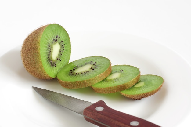 Plate with kiwi fruit sliced and knife on white background