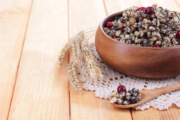 Тарелка с кутья - традиционная рождественская сладкая еда в украине, беларуси и польше, на деревянных фоне