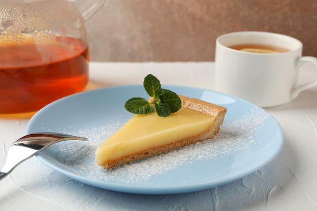 레몬 타트 슬라이스, 주전자와 흰색 테이블에 차 한잔 접시가 까이 서
