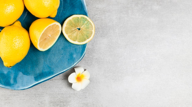 Plate with lemon on wooden background with copy space