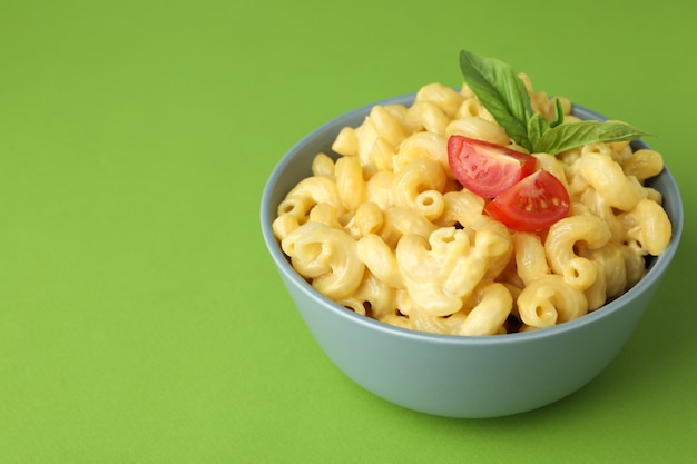Plate with macaroni and cheese on green background