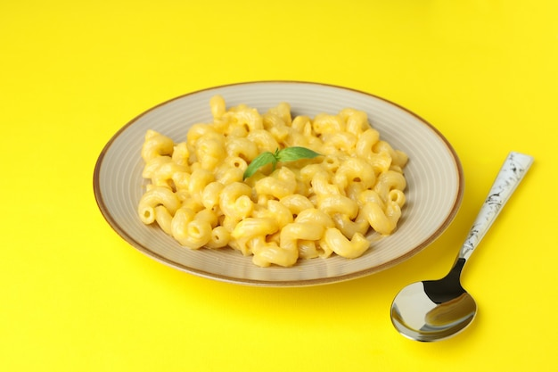 Plate with macaroni and cheese on yellow background