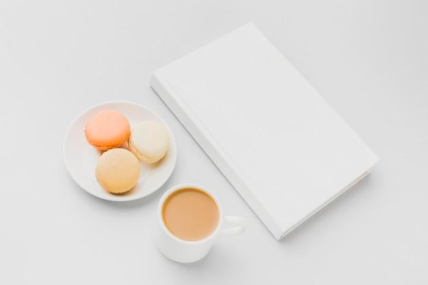 テーブルの上の本の横にあるマカロンとプレート