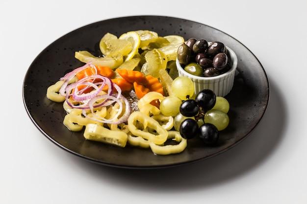 Тарелка с маринованными огурцами, перцем, луком и морковью с белым и черным виноградом и оливками
