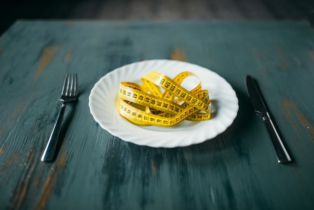 Plate with measuring tape on wooden table closeup. weight loss diet concept, fat burning