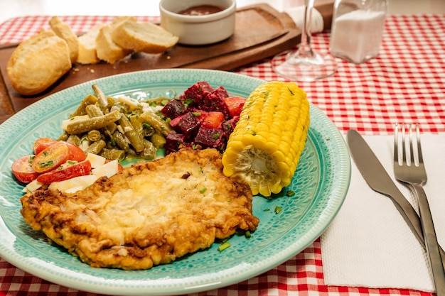 Plate with meat schnitzel, tomato salad, green beans, beetroot and hard-boiled egg and a corn cob on a traditional inn or restaurant table. horizontal view