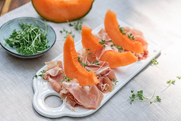 Plate with melon and jamon, wooden table, snack