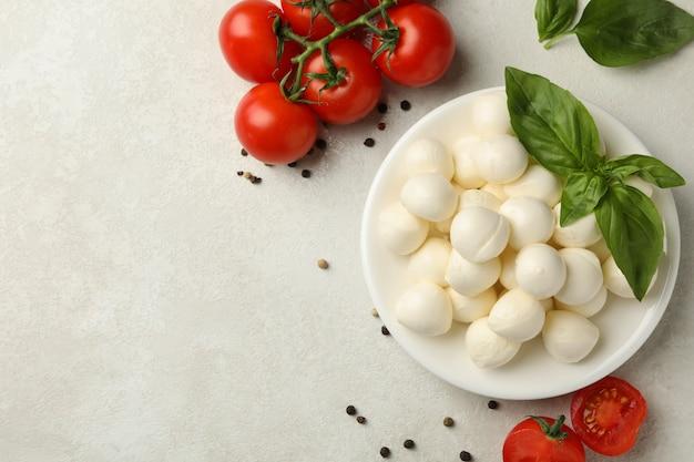 Тарелка с моцареллой и базиликом, помидорами и перцем на белом текстурированном фоне, место для текста