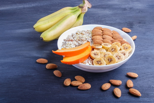 A plate with muesli, almonds, banana, persimmon on a black wooden background with copy space.