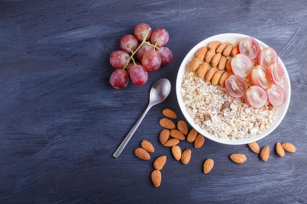A plate with muesli, almonds, pink grapes on a black wooden background.