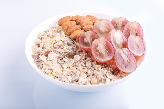 A plate with muesli almonds pink grapes isolated on a white background