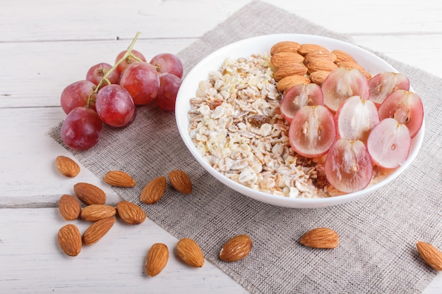 A plate with muesli, almonds, pink grapes on a white wooden background.