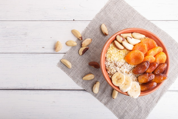 A plate with muesli, banana, dried apricots, dates, brazil nuts on a white wooden background.