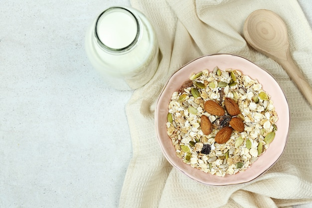 Plate with muesli, bottle of milk and wooden spoon on grey