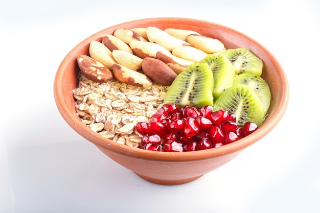 A plate with muesli, kiwi, pomegranate, brazil nuts isolated on white background.