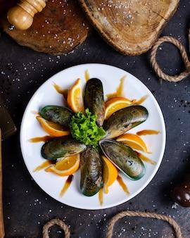 Тарелка с мидиями, подается с дольками лимона и листьями салата