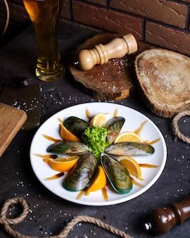 Тарелка с мидиями подается с ломтиками лимона