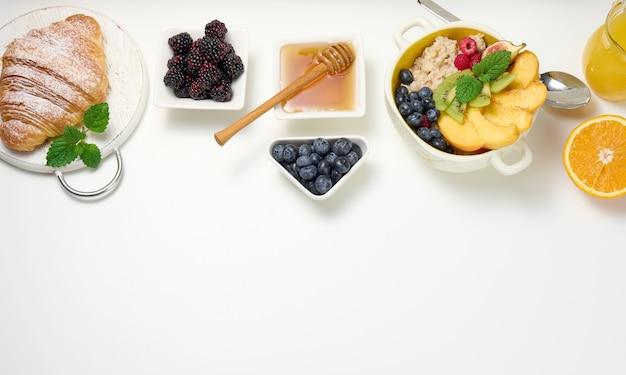 オートミールとフルーツ、半分熟したオレンジと絞りたてのジュースを透明なガラスのデカンターに入れ、白いテーブルのボウルに蜂蜜を入れます。健康的な朝食