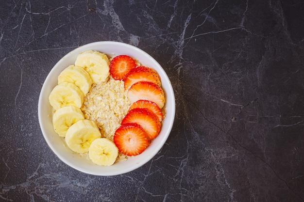Тарелка с овсянкой с нарезанной клубникой и бананом. концепция здорового завтрака, органические натуральные продукты, веганский. copyspace. вид сверху.
