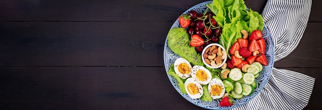 Plate with a paleo diet food. boiled eggs, avocado, cucumber, nuts, cherry and strawberries. paleo breakfast. top view