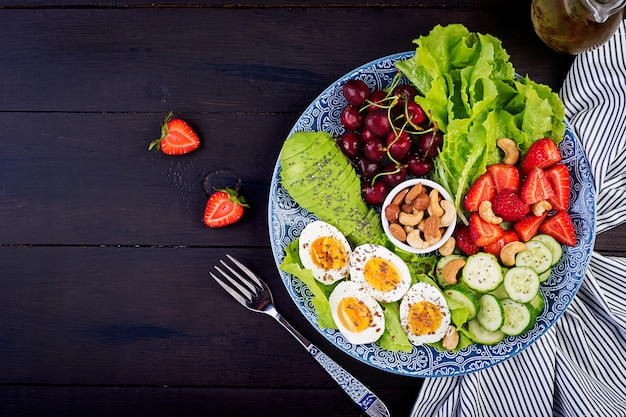 Plate with a paleo diet food, boiled eggs, avocado, cucumber, nuts, cherry and strawberries, paleo breakfast, top view
