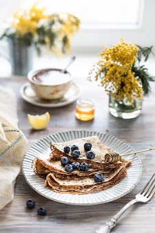 A plate with pancakes with blueberry berries on a wooden table.