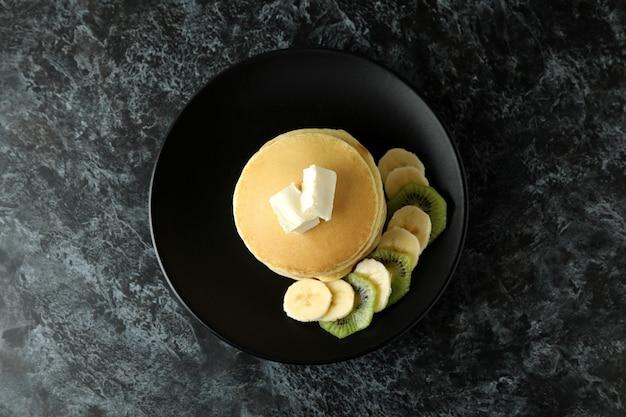 검은 스모키 테이블에 버터, 키위, 바나나와 팬케이크 접시