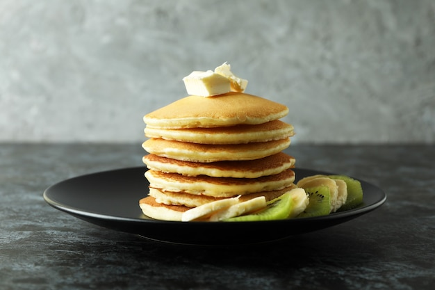 Plate with pancakes with butter, kiwi and banana on black smokey table